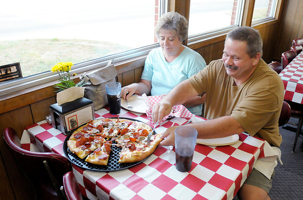 """Don Knight/The Herald Bulletin<br /> Gary and Kristy Webb of Anderson enjoy their pizza at Greeks Pizzeria in Anderson. """"We've never been disappointed here,"""" Gary said."""