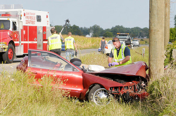 Don Knight/The Herald Bulletin<br /> A Sheriff's Department accident investigator documents the scene after a car left the roadway and hit a utility pole on Indiana 38 east of County Road 100 East on Thursday.