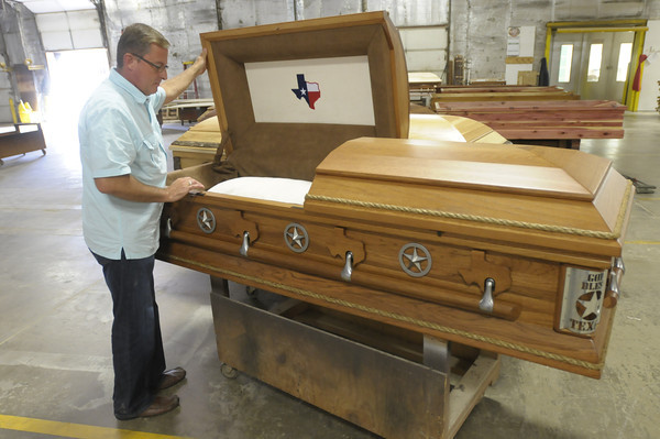 Don Knight/The Herald Bulletin<br /> Chris Boots, founder and president of C.J. Boots Casket Company,<br /> looks at a finished casket with a Texas inspired design. The company recently completed an audition tape for a reality T.V. show.