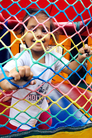 Marri Sipes, 2, enjoyed the bounce house but wanted to stay close to the window netting to help keep her balance and to keep close to her mother.