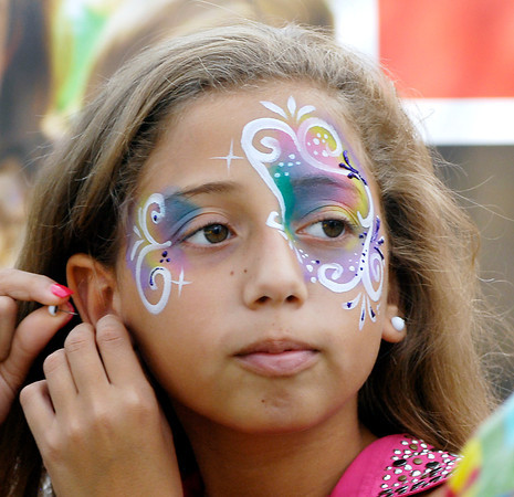 Ahniya Guajardo, 11, puts her earring back in after enjoying having her face painted Monday during the Labor Day Bash at Shadyside Park.
