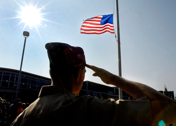 Collin Pratt, Company Commander of Anderson High School's Navy JROTC, salutes the flag as it is lowered to half-staff during Patriot's Day ceremonies Wednesday morning at AHS.