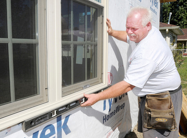 Don Knight/The Herald Bulletin<br /> Contractor Paul Shively checks the level of a window on a room addition. Shively's main supplier has been Carter Lumber. Carter closed their Anderson location last Tuesday.
