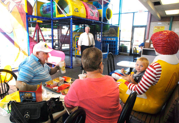 Ken and Sherry Sneed watch their great grandson Logan Hall,2, eats his  lunch in Ronald McDonald's lap at the McDonald's at 2830 Broadway in Anderson Thursday.  The restaurant will close next week to be torn down and a new facility built.  Ken Phillips, with McDonald's looks on in the background.