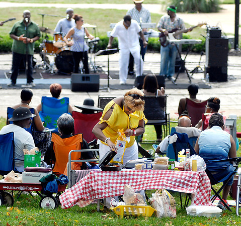 Vera Mitchem, of Anderson, fixes herself a plate of food as Toy Factory plays in the background during the Labor Day Bash at Shadyside Park.  Mitchem was there with family and friends as they set up their own picnic table with all their food to enjoy the festivities in the park.