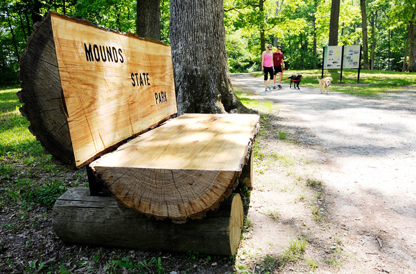 Don Knight | The Herald Bulletin file photo<br /> New benches built from a a large tree felled by a storm provide a resting spot while walking the trails at Mounds State Park. Running and walking the trails are a popular activity at the park and this Memorial Day the park is hosting a walking stick workshop.