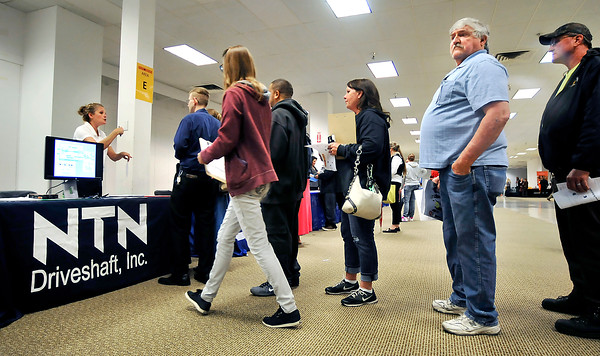 John P. Cleary   The Herald Bulletin<br /> Michelle Ferguson, H.R. generalist for NTN Driveshaft, talks to an applicant as a long line waits to get information on job openings at the Hire Anderson Job Fair Wednesday held at the former Sears store in the Mounds Mall.