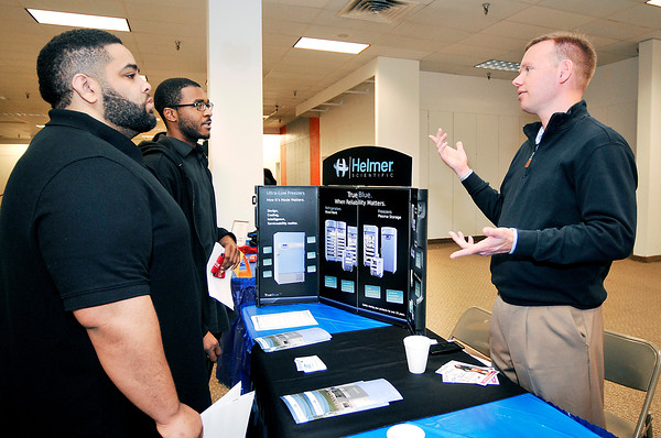 John P. Cleary | The Herald Bulletin<br /> Korey Moore and Brian Miles get information from Tim Miller of Helmer Scientific during the Hire Anderson Job Fair Wednesday at the Mounds Mall. Helmer Scientific is a medical device company from Noblesville.