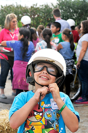 """John P. Cleary   The Herald Bulletin<br /> Anderson Elementary fourth-grader Isai Barron looks like a driver as he tries on the racing helmet and goggles during a """"Indiana Horses for Youth"""" field trip this past week for ACS fourth-graders."""
