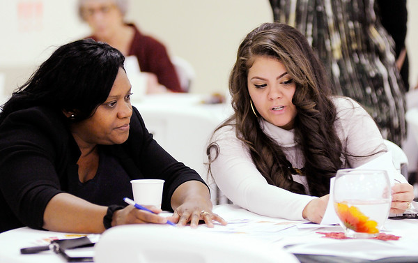 Don Knight | The Herald Bulletin<br /> Pathstone community development director Annette Phillips, left, and Impact Center assistant director Monique Flores go through a budgeting exercise as United Way of Madison County held a grand opening with their partners for the THRIVE Network office located at the Impact Center in Anderson on Tuesday.