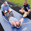 Don Knight | The Herald Bulletin<br /> Andrew Nelson completes situps while reserve officer Boomer Freeman holds his feet and officer Mike Stephens ensures he is meeting the standard and counts repetitions during a physical agility test for Chesterfield Police Department candidates at Highland Middle School on Wednesday.