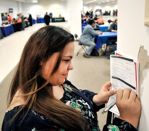 John P. Cleary   The Herald Bulletin<br /> Vanity Hammers uses a pillar to fill out a job application during the Hire Anderson Job Fair Wednesday at the Mounds Mall.