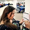 John P. Cleary | The Herald Bulletin<br /> Vanity Hammers uses a pillar to fill out a job application during the Hire Anderson Job Fair Wednesday at the Mounds Mall.
