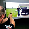 John P. Cleary | The Herald Bulletin<br /> Anderson Police officer Joe Garrett aims his gun at a subject as the person grabs a gun from his back pocket during this training video Friday.  APD officers have been going through training using the FATS video system this week on what level of force to use in different scenarios.