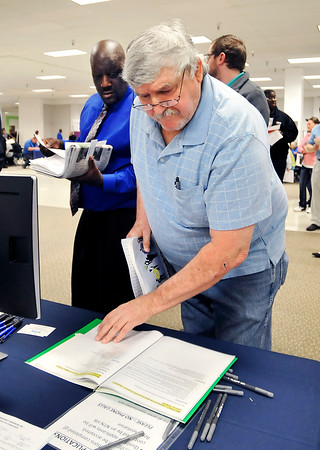 John P. Cleary | The Herald Bulletin<br /> Mark Murdock, of Anderson, looks over the job descriptions of positions at NTN Driveshift during the Hire Anderson Job Fair Wednesday.