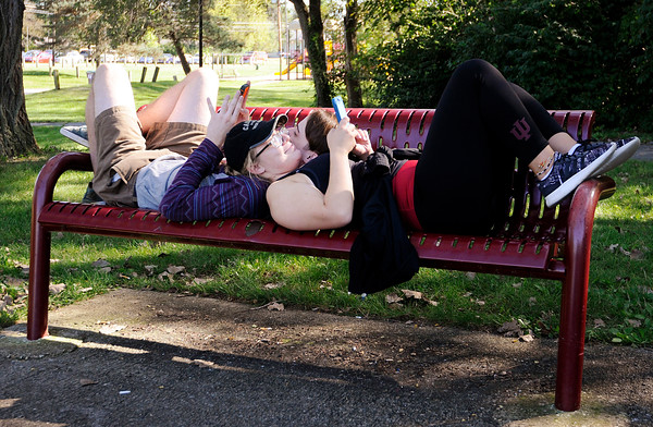 Don Knight   The Herald Bulletin<br /> Jacob Ritchie and Phoebe Mangas  lay on a park bench while playing Pokémon GO at Shadyside Park on Thursday.