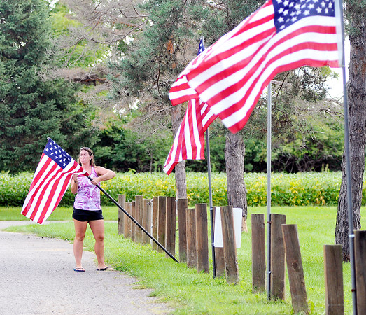 John P. Cleary   The Herald Bulletin<br /> Betsy Lamb, assistant manager of the Dolphin Club, puts up American Flags along the driveway of the facility Friday afternoon for the upcoming Labor Day holiday weekend.