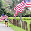John P. Cleary | The Herald Bulletin<br /> Betsy Lamb, assistant manager of the Dolphin Club, puts up American Flags along the driveway of the facility Friday afternoon for the upcoming Labor Day holiday weekend.