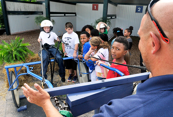 """John P. Cleary   The Herald Bulletin<br /> Edgewood Elementary fourth-grader Gage Dunkin, 10, handles the reins as he sits in a sulky to get the feel of a driver at Hoosier Park during a """"Indiana Horses for Youth"""" field trip this past week for ACS fourth-graders."""