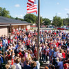 """Students and staff of Robinson Elementary sing """"The Star-Spangled Banner"""" as the American flag is raised<br /> to half-mask on Friday during Red, White and Blue Day activities."""