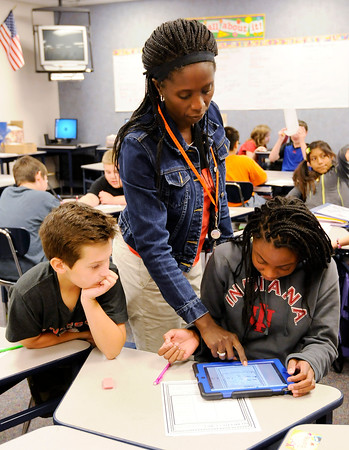 Don Knight | The Herald Bulletin<br /> Catrina Cooper gives Ahryiele Woods instruction as she answers a question on a tablet connected to the classroom's overhead projector as Harrison Mudd looks on at Anderson Elementary on Thursday.