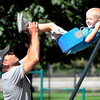 John P. Cleary | The Herald Bulletin<br /> Mike Mills, of Lapel, reaches high to swing his 5-year old son Oakland by the legs as they play on the playground at Falls Park in Pendleton Wednesday afternoon. With above normal temperatures and sunshine, people were out enjoying the last full day of summer.