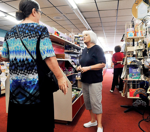 John P. Cleary   The Herald Bulletin <br /> Beverly Cox, center, owner of Cox Gift Shop in Alexandria, helps a customer during her clearance sale to close the store after 60 years in business.