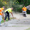 John P. Cleary |  The Herald Bulletin<br /> Anderson Street Department workers Justin Ancil and Rodney Robbins spread out gravel as work continues to widen the trails around Shadyside Park in preparation for resurfacing the paths starting later this week. Marquise McCloud, right,  runs a sweeper cleaning the pathway as they work toward him.