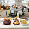 John P. Cleary |  50-Plus tab<br /> As Bob Armstrong addresses the Keenagers group the lunch table as been set and ready for the members to enjoy.