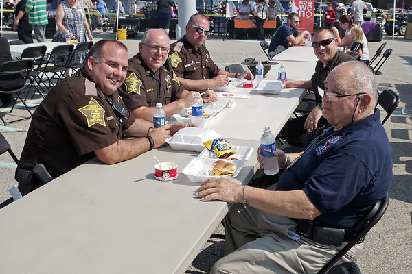 "Madison County police officers Andy Williams, John Owen, David Kolros and Darren Dyer, along with Jeff Ehrhart of the Chesterfield-Union Township Volunteer Fire Department, enjoy lunch at the 2017 ""Honor the Badge"" event at the Mounds Mall."