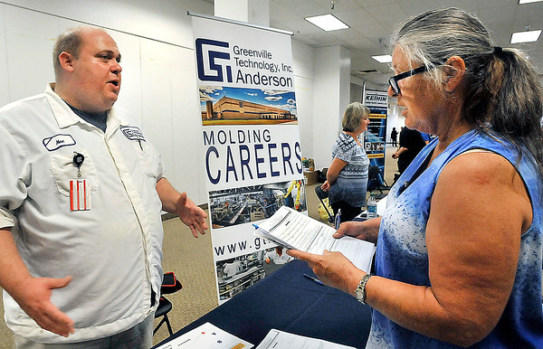 John P. Cleary |  The Herald Bulletin<br /> Moe Claypool, of Greenville Technology, Inc. Anderson, talks with Marcia Swindell, Fairmount, about the job opportunities offered at GTI during the HireAnderson Job Fair Thursday.