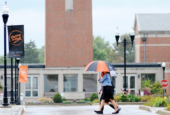 Don Knight   The Herald Bulletin<br /> A trio of students walk under a pair of umbrellas as they cross 5th Street during a light rain on Wednesday. The National Weather Service is forecast an end to the scattered rain today and nice weather for the rest of the week.