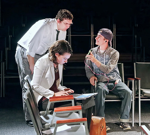 "While awaiting their flight at the airport, Marcy (Alaina Porch) works on her sales presentation while her business partner Ben (Gabe Porch) checks out Toby's (Stephen Hartzell) phone app in ""Standby"" at the Alley Theatre."