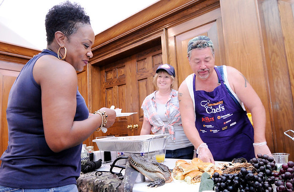 Don Knight | The Herald Bulletin<br /> Ivy Tech Chancellor Jim Willey serves alligator sliders during the Community Chefs fundraiser at the Anderson Country Club on Saturday. Chef Ryan Bell from Ivy Tech's culinary school smoked the alligator for 12 hours.