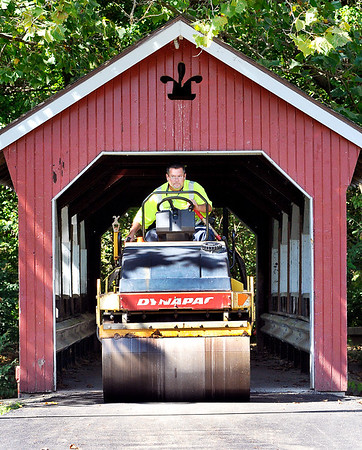 John P. Cleary |  The Herald Bulletin<br /> Corey Dickey, of the Anderson Street Department, has to duck his head as he comes through the covered bridge at Shadyside Park on his paving roller. Dickey was driving the roller back to it's trailer after his co-workers had finished up paving the trails around the north end of Shadyside Park Monday afternoon.