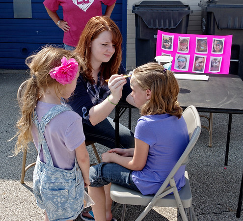 """As her sister Penny watches, Nevaeh Baker of Elwood gets her face painted by artist Kenzie Burton during the """"Honor the Badge"""" event supporting those serve in the public safety arena."""