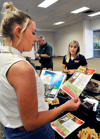 John P. Cleary |  The Herald Bulletin<br /> Jessica Cook, Anderson, looks over information that Michelle Musgrave, corporate recruiting for Red Gold, has given her during the City of Anderson's HireAnderson Job Fair Thursday.
