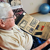 John P. Cleary |  The Herald Bulletin<br /> WWII Army veteran Virgil Stamm recently made the Indy Honor Flight to Washington D.C. Virgil looks over his scrapbook of memories.