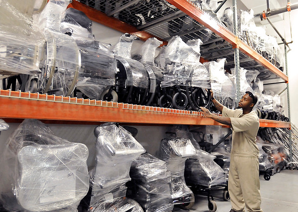 John P. Cleary |  The Herald Bulletin<br /> Keayon Scott checks the warehouse where these racks of wrapped finished wheelchairs wait to be shipped out.