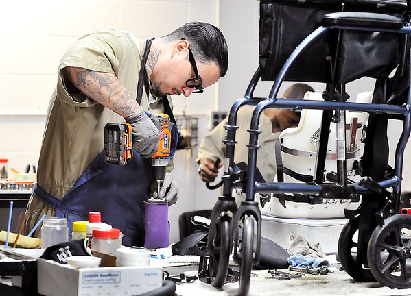 John P. Cleary |  The Herald Bulletin<br /> Juan Gonzalez works at his work station in the wheelchair shop in the Correctional Industrial Facility refurbishing this wheelchair for the Wheels for the World program.