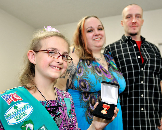 John P. Cleary |  The Herald Bulletin<br /> Girl Scout Melina Lakey, 9, holds the Girl Scout Medal of Honor she has just received as her parents, Ashley McCollum-Lakey and Jeff Lakey look on. Melina was given the honor for her quick thinking and calmness under pressure in rescuing her mom after a SUV crash.