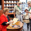 John P. Cleary | The Herald Bulletin<br /> Nancy Schaar, right, checks out a CD as her husband, Roger, watches Gloria Gaither autograph his book during Gloria's book signing Friday at the Gaither Fall Festival. The Schaars are from Elk River, MN.