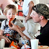John P. Cleary | The Herald Bulletin<br /> 21 month old Cohen Gill takes a big bite of the hot dog is father, Eli Gill, offers him during the Madison County Solidarity Labor Council's annual Labor Day picnic Monday.