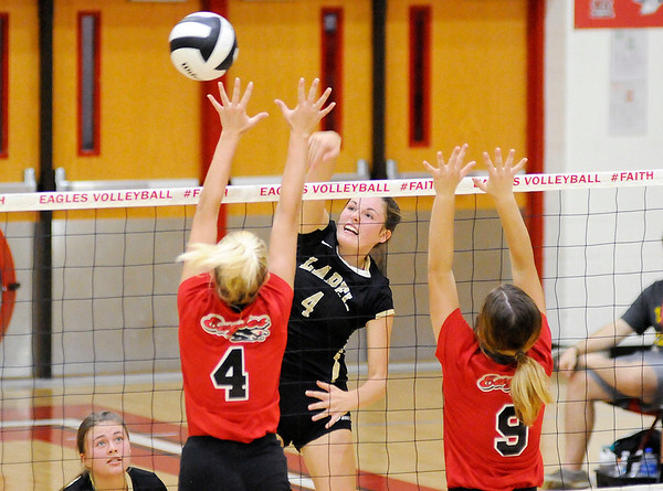 Don Knight   The Herald Bulletin<br /> Lapel's Zoe Freer attacks the ball as Frankton's Audrey Cleek (4) and Jaylen Lovett (9) attempt to block her on Wednesday.