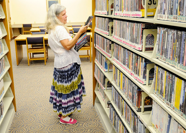 Don Knight   The Herald Bulletin<br /> Cinthia Reeves looks for DVDs at the Anderson Public Library on Tuesday. The library has eliminated late fees effective September 1st.