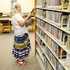 Don Knight | The Herald Bulletin<br /> Cinthia Reeves looks for DVDs at the Anderson Public Library on Tuesday. The library has eliminated late fees effective September 1st.