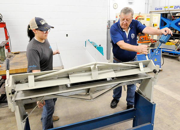 Don Knight | The Herald Bulletin<br /> Malcolm Stalcup, right, helps Emily Isaac bend a piece of metal using a finger break at the Hinds Career Center in Elwood on Tuesday. Stalcup is one of five Indiana skilled trades teachers named as a semi-finalist for the Harbor Freight Tools for School prize.