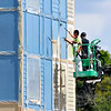 John P. Cleary | The Herald Bulletin<br /> Workers use a lift to apply a coating of paint onto the exterior of the Fieldhouse Apartments being built on West 14th Street next to the Wigwam Monday afternoon.