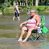 John P. Cleary | The Herald Bulletin<br /> Debbie Messinger, of Indianapolis, sits in her chair in the middle of Fall Creek in Pendleton at Falls Park Monday as she watches her grandchildren play in the water. Nine members of her family came to Pendleton to spend their Labor Day holiday enjoying the park and the water.