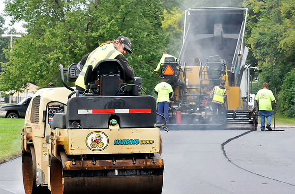 John P. Cleary   The Herald Bulletin<br /> Dale Pierson, of Harding Group of Indianapolis, watches his line as he goes backwards on his roller as his co-workers lay down a fresh surface of asphalt to the entrance road of Anderson High School's D26 Career Campus Thursday afternoon.